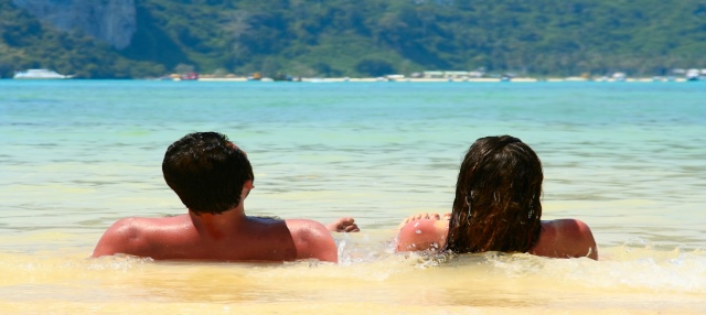 Young couple relaxing side by side in the surf on a beautiful beach.